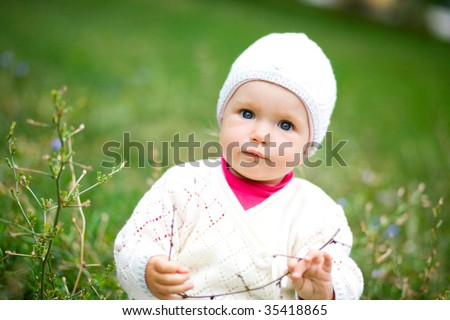 Small child in a grass. Looks in a camera.