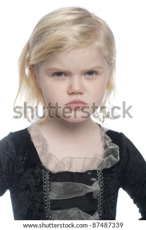 Small child is dressed in a pirate costume and is looking directly at camera. She has a angry expression on her face