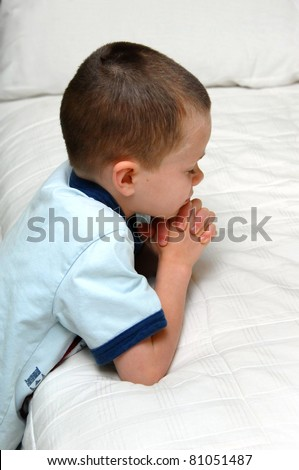 Small child kneels besides his bed and folds his hands in prayer.  He is wearing a blue shirt and kneeling besides a white covered bed.