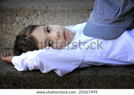 small child looking into the camera laying down