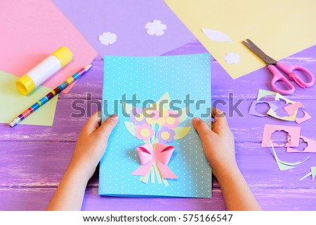 Small child made a greeting card with flowers for mom. Step. Child holds a card in his hands. Tools and materials for children\'s art creativity on table. Mother\'s day or March 8 greeting card DIY idea
