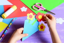 Small child makes paper crafts for mother's day or birthday. Small child doing paper flowers for mom. Simple nice kids gift idea to mom. Scissors, glue stick, flowers templates, pencil on a wood table