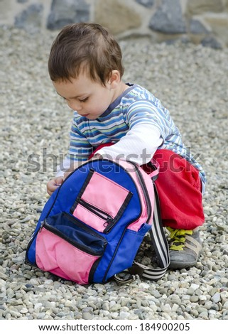 Small child or toddler opening his backpack or bag  while crouching on the ground.