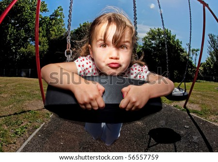 Small child playing on colourful swing in a sunny playground or family park