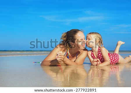 Small child playing with fun and kissing happy young mother smiling with love to her daughter lying on wet sand sea beach. Family lifestyle and summer vacation with children on tropical island resort