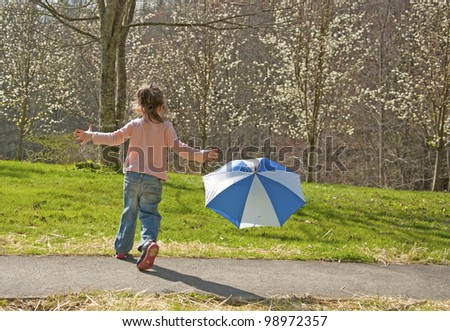 Small child plays with an umbrella on a windy day.