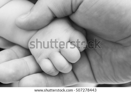 small child's hand in hand of adult parent closeup / black and white photo in retro style