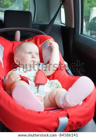 Small child sits in the automobile armchair, fastened by seat belts.