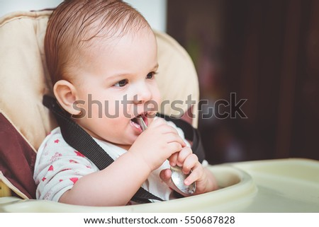 small child sits on a chair and eating with spoon #550687828