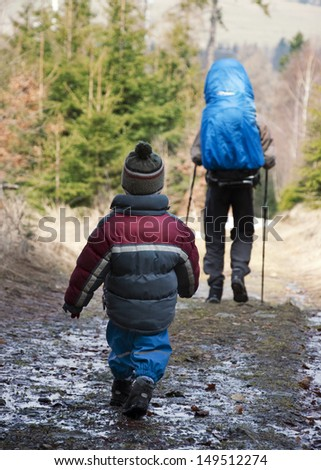 Small child walking or hiking through the forest behind his father.