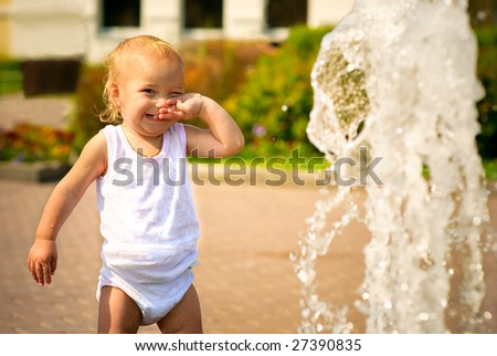 Small child wipes person on whom water from fountain has got.