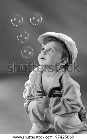 small child with soap bubbles on the background wall