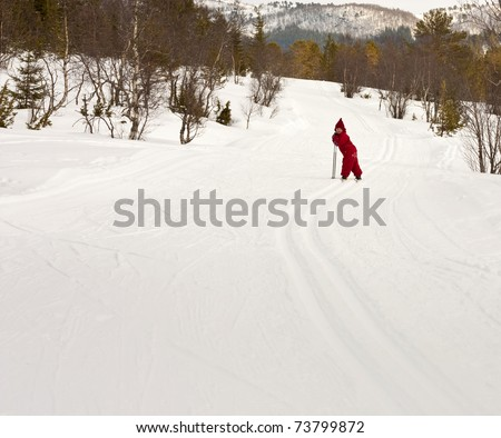 Small child (4 years old) skiing in the forest