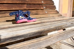 Small childlike shoes on old  wooden bench