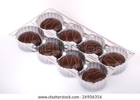 Small chocolate cakes covered with a layer of black chocolate and decorated with a pattern from a milk chocolate.
