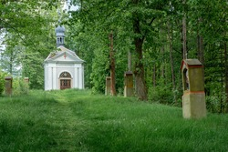 Small Christian Holy Trinity Chapel with Stations of the Cross in front of it in Brtniky, Bohemian Switzerland, Czech Republic. Words in Czech saying
