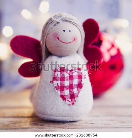 Small christmas angel with red wings Family and child christmas gifts.Christmas decoration Colorful window in the city during winter