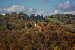 Small church on the mountain slope surrounded by colorful forest, beautiful autumn alpine landscape with blue cloudy sky. Alps mountains in Slovenia, outdoor travel background