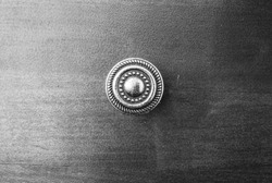 small circle handle on wood drawer with black and white vintage filter