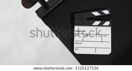 Small Clapper board or movie slate with director chair use in video production ,film and cinema industry. It's put on white background. #1520127536