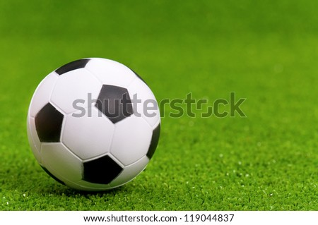 Small classic soccer ball on green artificial grass