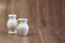 Small clay ceramic blank vases for painting close-up on a dark wooden background