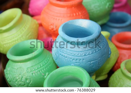 Small clay pots in various colors with religious text inscribed for Diwali festival celebration rituals in India.