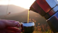 Small coffee pot on a background of mountain landscape, coffee pouring into a mug