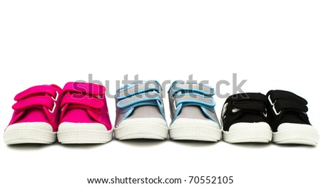 Small color children shoes isolated on white background in row