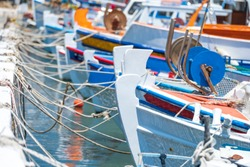 small colorful Greek fishing boats are tied up with rope in a small tourist port in Greece