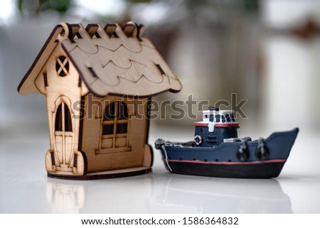 small copy of a small wooden house and a ship blue with red stripes