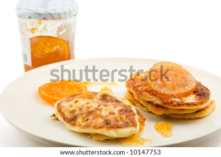 small cottage pancakes with some orange jam, jam jar in background, isolated on white