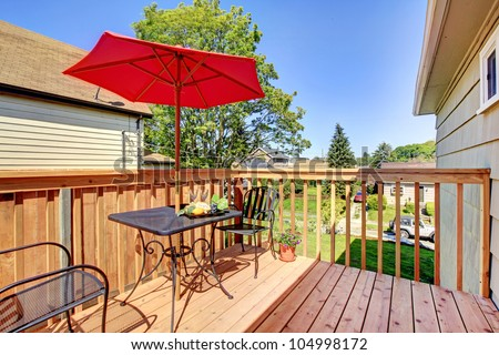 small cozy deck with red umbrella.