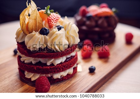 Small cream cake wit berries and physalis decoration on wooden plate #1040788033