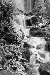 Small creek falling down between rocks . A frosty day in winterseason.