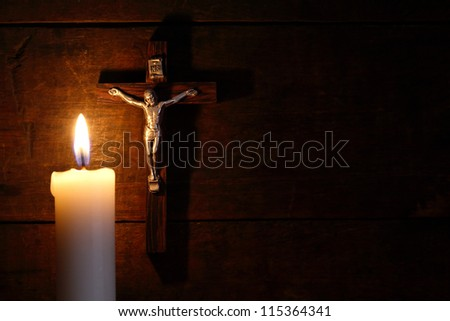 Small crucifix hanging on old wooden wall near lighting candle