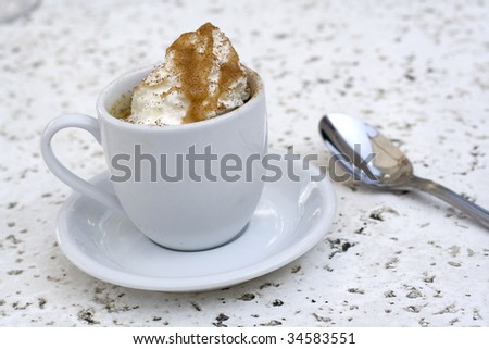 Small cup of bananas foster dessert with whipped cream and caramel drizzled on top.