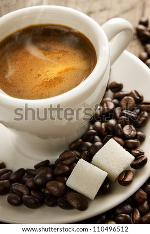 Small cup of black coffee on a brown background with coffee beans