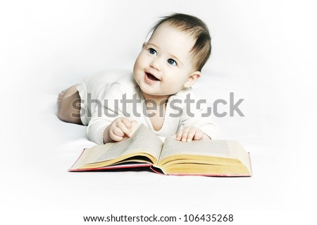 Small cute baby lying with a book