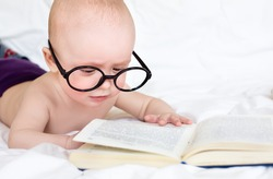 Small cute baby try to read a book