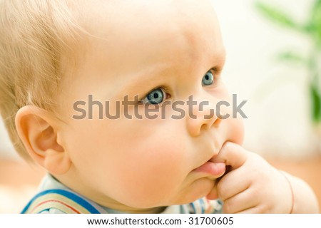 Small cute baby with finger in mouth
