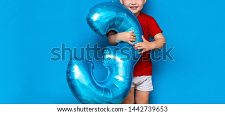 small cute blonde boy on blue background holding foil-coated sphere baloon blue colour. happy birthday three years old.