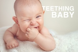 Small cute funny baby infant teething with face expression hands and fingers in mouth sore gums soothe