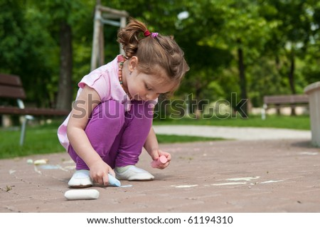 Small cute girl drawing with chalk on sidewalk, trees in background