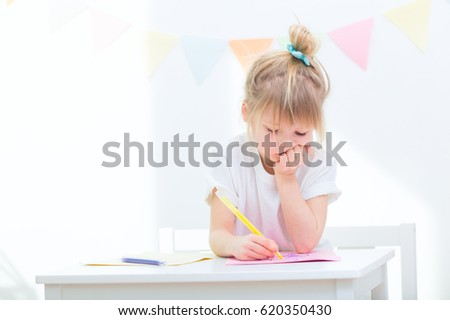 small cute girl of elementary school age sitting at table and learning to draw or write indoors. child painting with colored pencils at home or kindergarten #620350430
