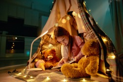 Small cute girl wearing pyjamas sitting on a floor barefoot in a self-made hut made of a plaid, playing games on tablet, having her teddybears and garlands around in a spacy room