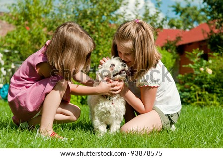 Small cute girls playing with her dog in garden behind family house