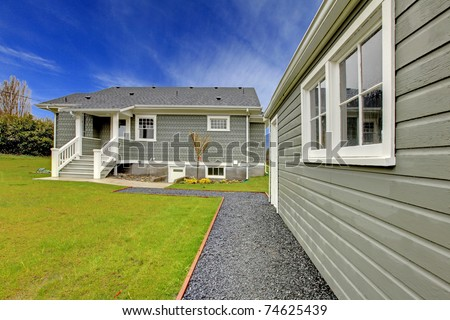 Small cute grey New England style home with matching detached garage.