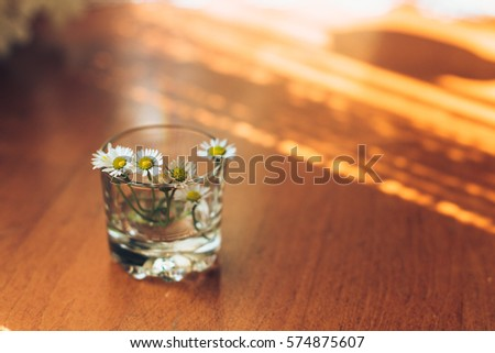 Small daisies in glass vase on the wooden background. #574875607