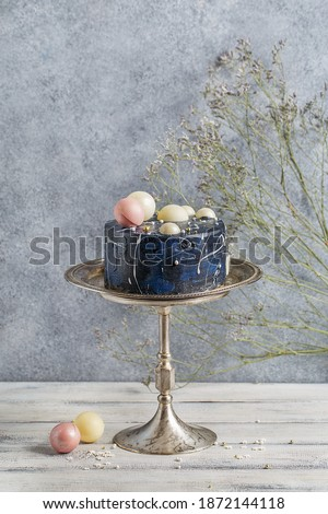 Small dark blue frosted cake decorated with white chocolate balls on silver cake stand over white background with flowers and vintage cake spatula. Side view, copy space Foto stock ©
